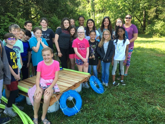 Overall Creek Elementary parent Chrystal Pandolfo, far right in back, stands with fifth grade students of Tara Klarer (back row, third from the right) in front of their boat project.
