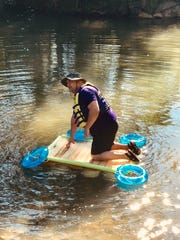 Overall Creek Elementary principal Don Bartch climbs onto a boat designed and built by fifth grade students of Tara Klarer. The boat project is one the entire fifth grade participates in as part of a yearly STEM learning. The boat stayed afloat during the brief voyage across nearby Overall Creek.