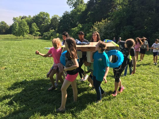 Fifth grade students of Overall Creek Elementary teacher Tara Klarer carry the boat they designed as part of a STEM project. The boat managed to carry their principal, Don Bartch, onto Overall Creek, located behind the school.