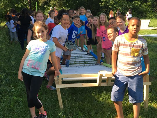 Overall Creek Elementary fourth grade students stand in front of a ramp they built to launch boats designed and built by fifth graders.
