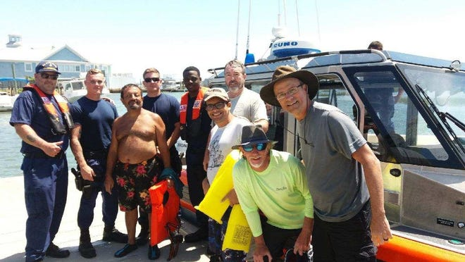 Five men from Granville's Spring Hills Baptist Church pose with the Coast Guard crew which rescued them about six miles off the coast of Pawleys Island, South Carolina. From left are Dr. Mourad Abdelmessih (without shirt), his son Andrew (glasses), Jeff Houghton (behind Andrew), Tim Deaver and Dr. Glen Kain.