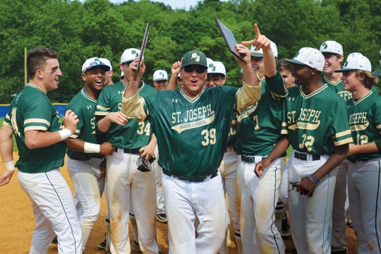 St. Joseph head coach Mark Cieslak holds up the trophies after getting iced on the field. The Green Knights defeated Bergen Catholic, 3-1, for the Bergen County baseball title at Northern Valley Demarest High School on Sunday, May 29, 2016.
