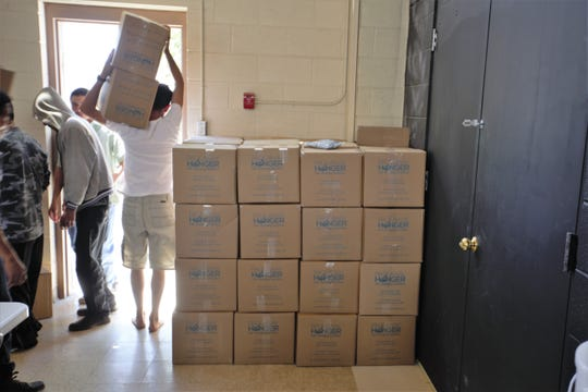 Migrants receiving aid at the former U.S. Army Reserve Center in Las Cruces assist with moving cartons of donated non-perishable meals on Friday, May 17, 2019.