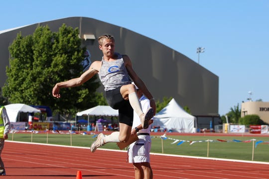 Carlsbad's Austin Atencio flies into the dirt in the 5A boys long jump during Friday's state track and field championships in Albuquerque. Atencio won the event with a new Class 5A state record 23 feet, 1 3/4 inches.