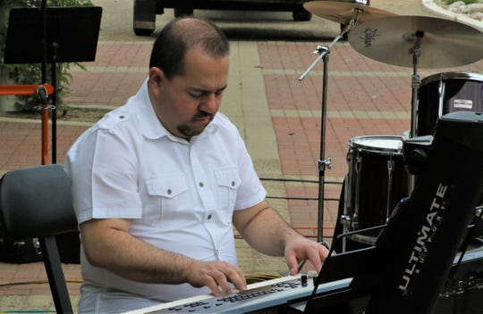 Mauricio Espinal plays keyboards during a benefit concert for his family May 16 on the patio at the Farmington Museum at Gateway Park.