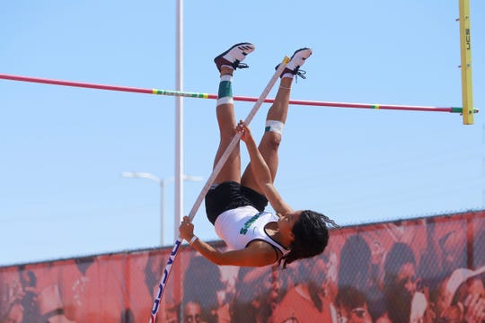 Farmington's Kiara Quezada dives over the bar in the 5A girls pole vault during Friday's state track and field championships in Albuquerque. Quezada won her third straight girls pole vault title with a new Class 5A record of 12 feet, zero inches.