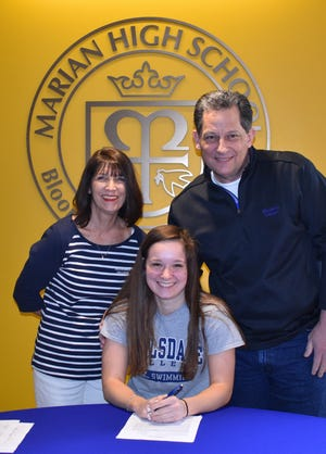 Marian senior Anika Fassett with her parents Marily and Dennis Fassett standing behind her, signed a national letter of intent to swim in college next year.