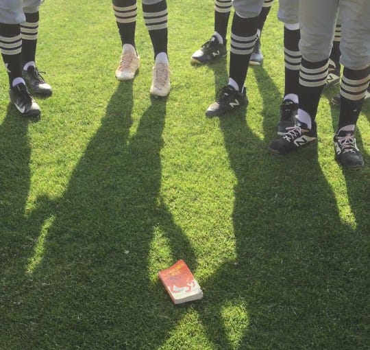 """A well-worn copy of the novel """"Catcher in the Rye"""" is on the ground as the Xavier Prep baseball team stands in a circle after another win. The book has become the team's good-luck charm."""