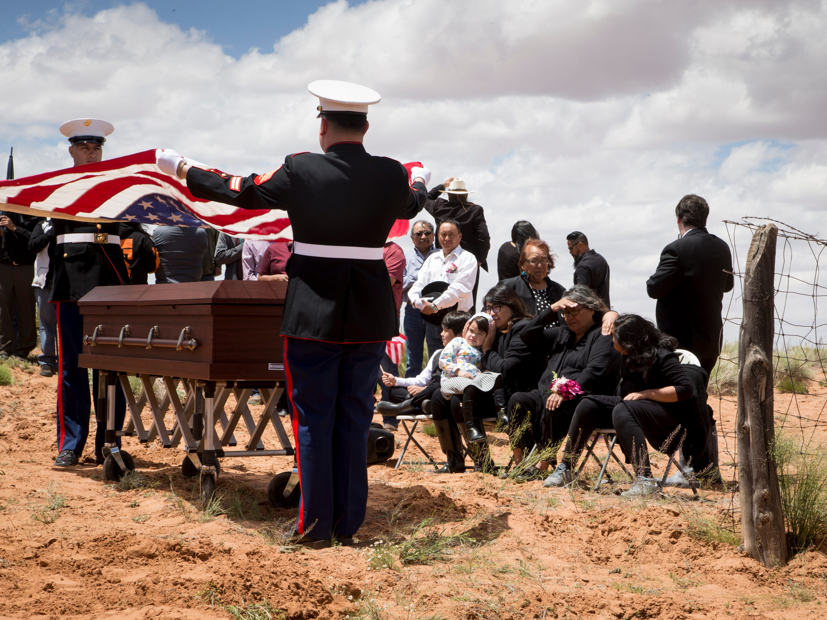 The flag was folded and presented to family (right, seated) during the interment of Navajo Code Talker Fleming Begaye Sr. on May 17, 2019, at the family plot in Salt Water Canyon, Ariz.