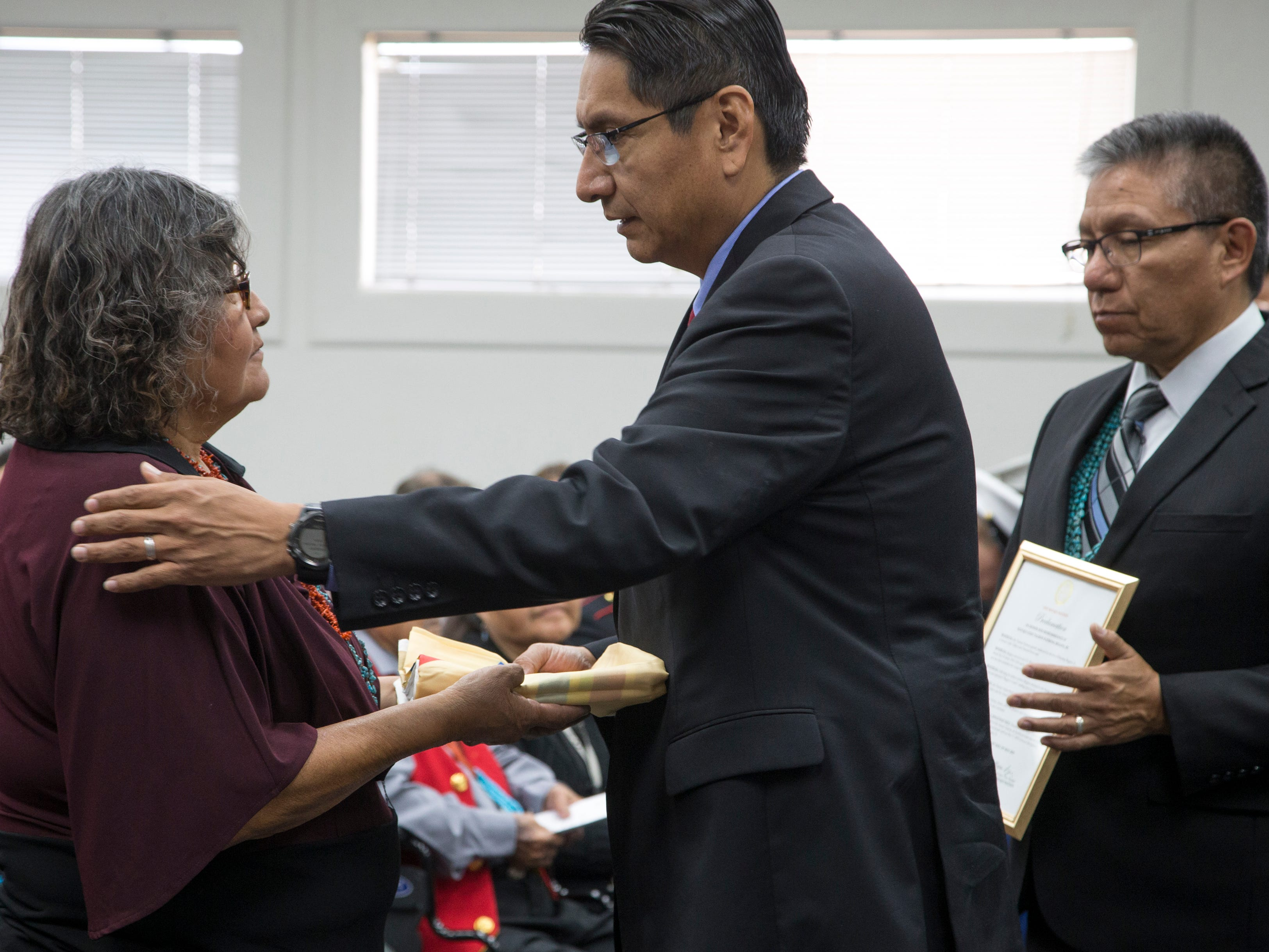 Navajo Nation President Jonathan Nez (center) presents Veronica Walter (left, daughter) a flag during the funeral service for Navajo Code Talker Fleming Begaye Sr. at the Potter's House Christian Center in Chinle, Ariz., on May 17, 2019.