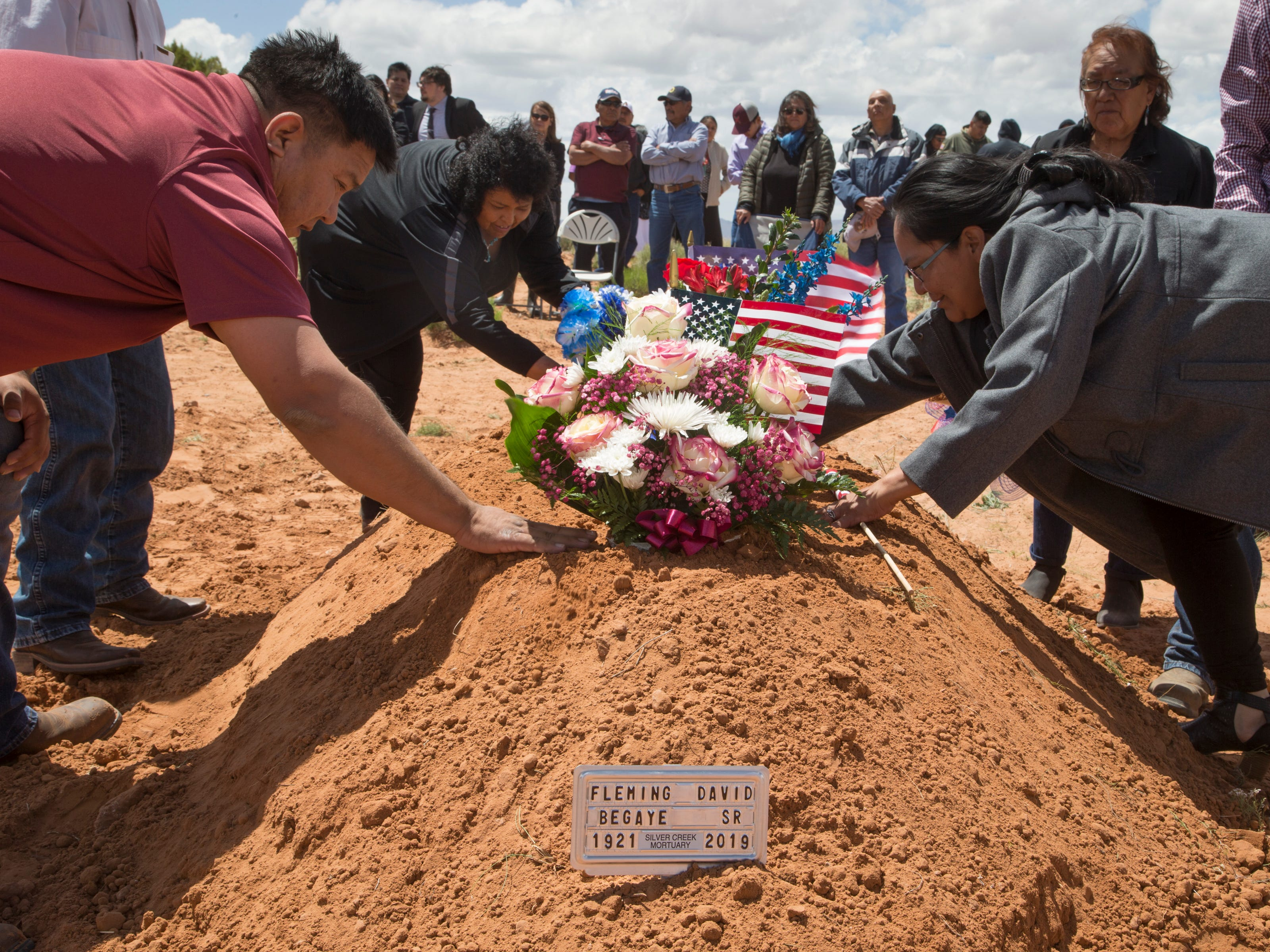 Family and friends place flowers on the grave during the interment of Navajo Code Talker Fleming Begaye Sr. on May 17, 2019, at the family plot in Salt Water Canyon, Ariz.