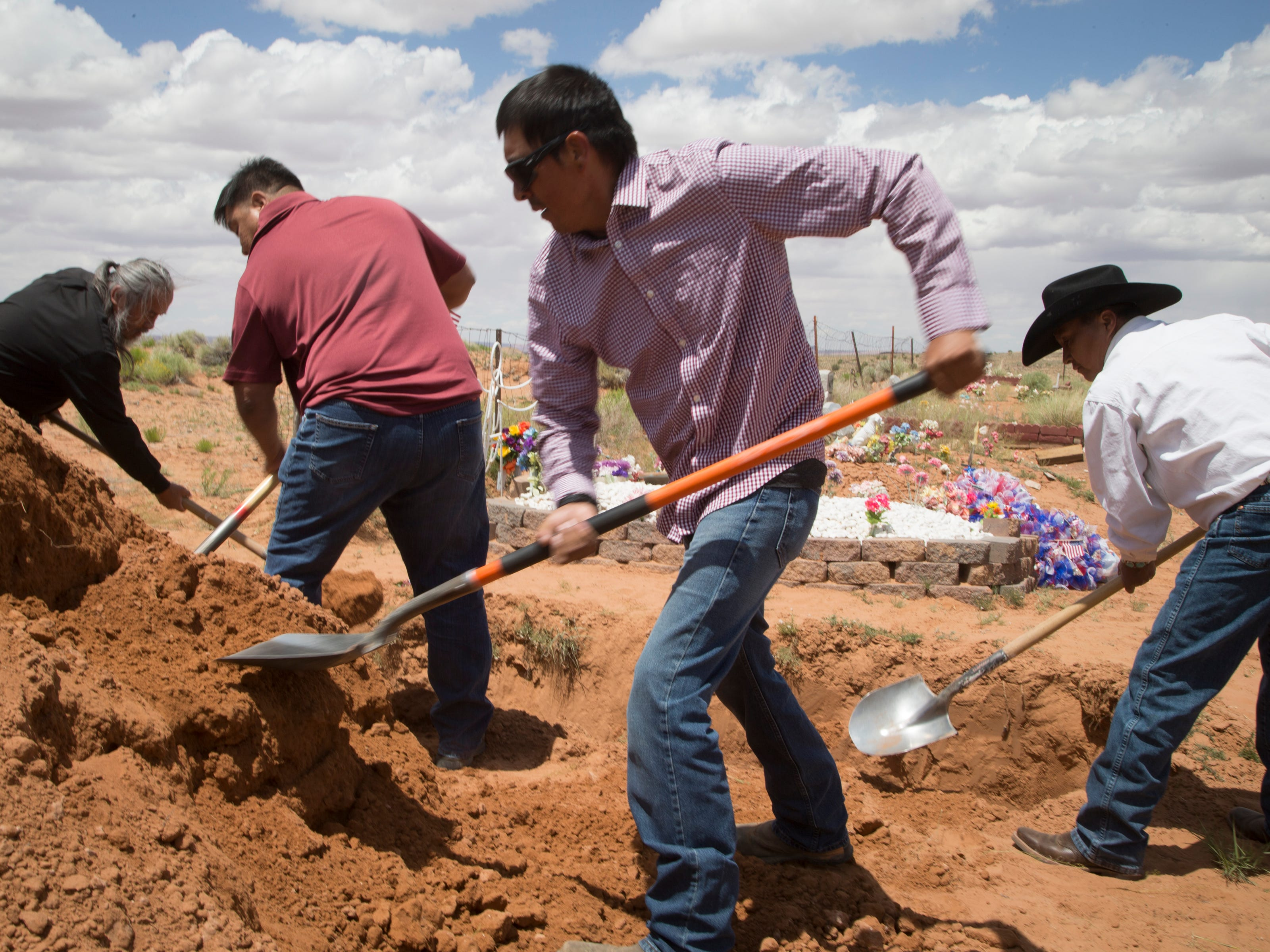 Family and friends fill in the grave during the interment of Navajo Code Talker Fleming Begaye Sr. on May 17, 2019, at the family plot in Salt Water Canyon, Ariz.