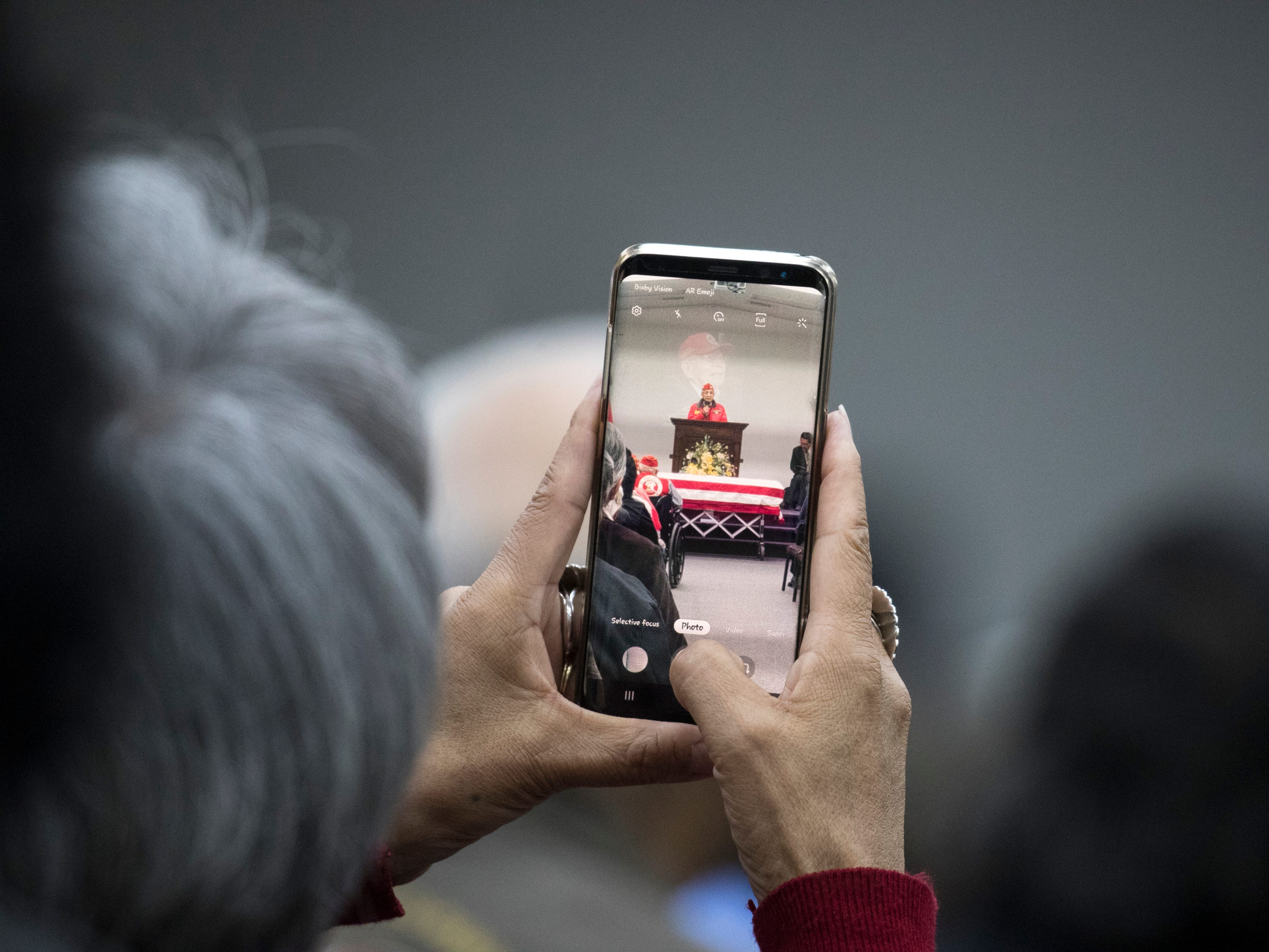 Navajo Code Talker Peter MacDonald Sr. is videoed during the funeral service for Navajo Code Talker Fleming Begaye Sr. at the Potter's House Christian Center in Chinle, Ariz., on May 17, 2019.