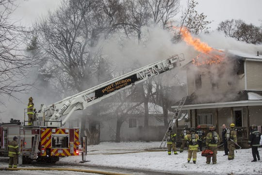 Members of the Port Huron Fire Department work the scene of a house fire in February 2016 at the corner of 11th and Cedar streets.