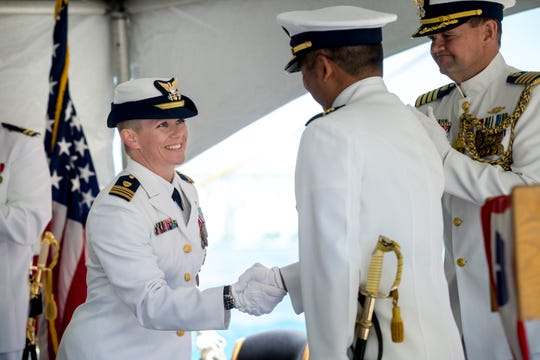 U.S. Coast Guard Lt. Commander Molly Waters shakes hands with Commander Justin Kimura as she relieves him of his duty as Commanding Officer of the U.S. Coast Guard Cutter Hollyhock during a change of command ceremony Friday, June 17, 2016 in Port Huron.