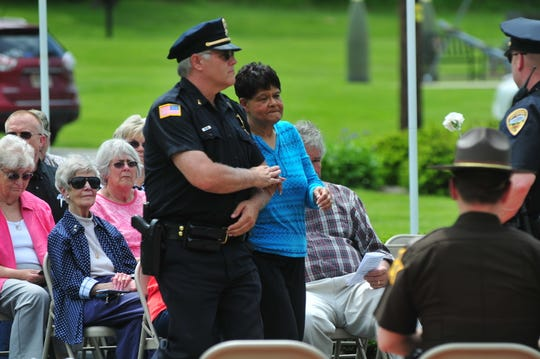 Lt. Donnie Benedict escorts Judy Spicer for Spicer to place a flower in honor of her father, former Richmond Police Department Officer Wilson Spicer, during Friday's Peace Officers Memorial Service.