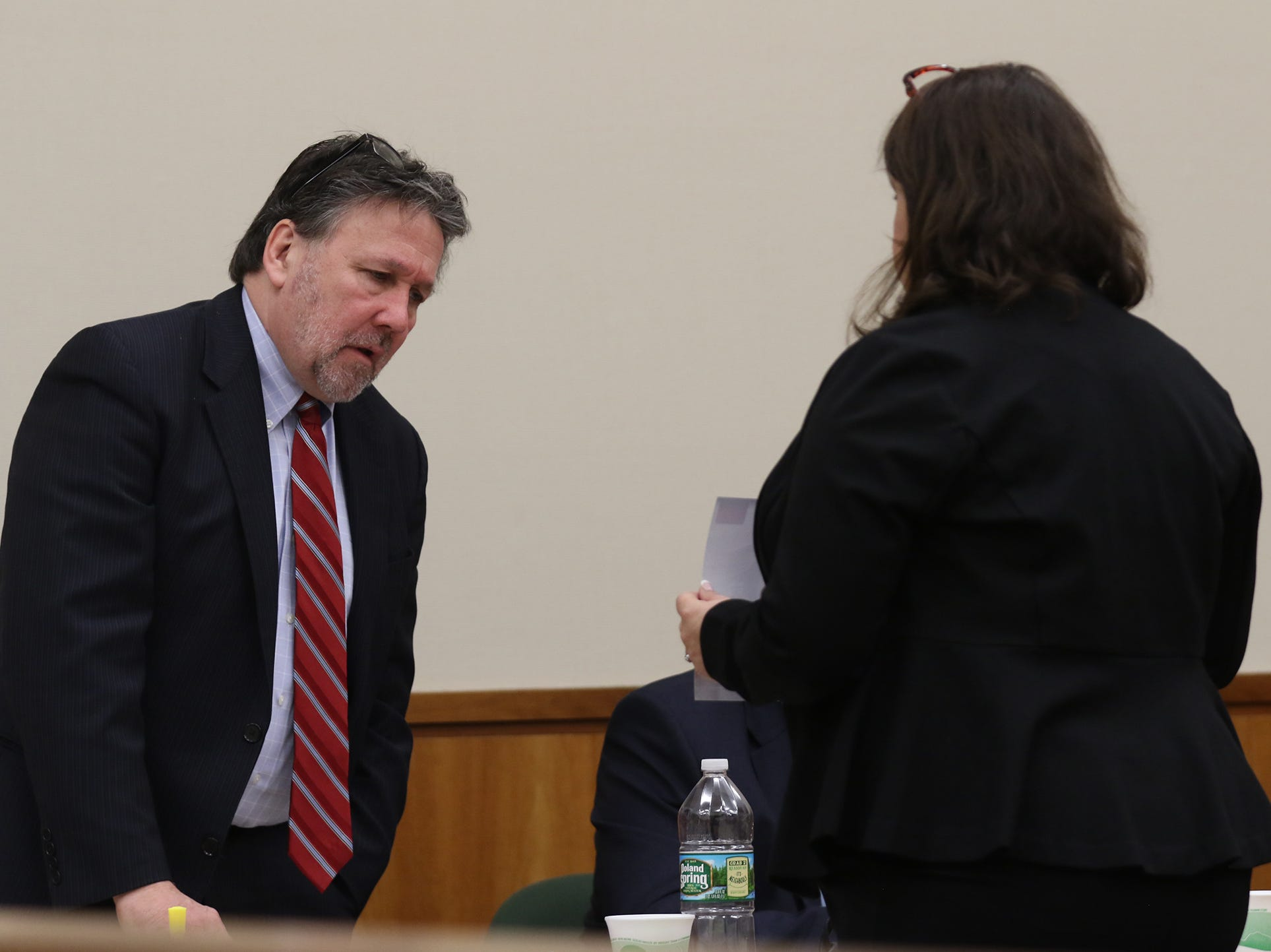 Clark Zimmermann looks at a photo of Christopher Pate taken when Pate was brought to the hospital after his arrest.  Gina Clark, asst. district attorney, is about to introduce the photo into evidence.