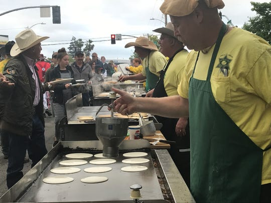 John Luntey of the Asphalt Cowboys fills up the grill with pancakes at Friday's event.