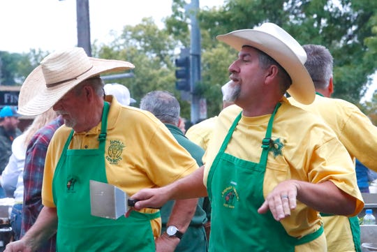 Asphalt Cowboy John Carelli, right, does a flapjack dance Friday, May 17, 2019, as he and his father, Fred Carelli, left, cook during the annual pancake breakfast for Rodeo Week.