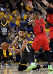 Golden State Warriors guard Stephen Curry, bottom, passes the ball as Portland Trail Blazers guard Damian Lillard (0) and center Enes Kanter defend during the second half of Game 2 of the NBA basketball playoffs Western Conference finals in Oakland, Calif., Thursday, May 16, 2019.