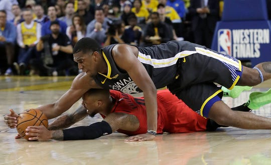Golden State Warriors center Kevon Looney, top, reaches for the ball over Portland Trail Blazers guard Damian Lillard during the second half of Game 2 of the NBA basketball playoffs Western Conference finals in Oakland, Calif., Thursday, May 16, 2019.
