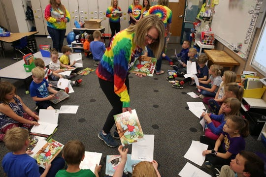 Kim Oaks, Caitlyn Carman's aunt, hands out books to first grade students at Robert Frost elementary May 17 as part of the Live Like Cat Foundation.