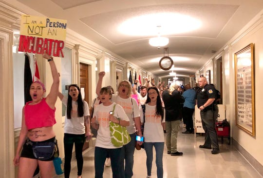 Protesters march through the halls of the Missouri Capitol outside the House chamber on Friday, May 17, 2019, in Jefferson City, Missouri, in opposition to legislation prohibiting abortions at eight weeks of pregnancy. Missouri's Republican-led Legislature has passed a sweeping bill to ban abortions at eight weeks of pregnancy, and Republican Gov. Mike Parson is expected to sign it. The House approved the measure Friday May 17, 2019.