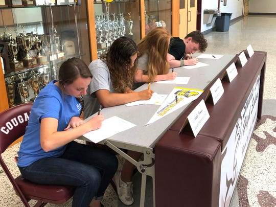 Maddie Renner, Maddie Varner, Hannah Chatterton, and Jesse McCauley sign celebratory paperwork Friday after announcing their college choices.