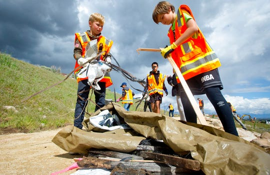 In a Wednesday, May 8, 2019 photo, Brenton Cramer, 10, left, and Damon Haub, 10, both of Lehi, gather trash into a pile as he and other volunteers help to complete an Eagle Scout Service Project that aims to create a walkable path connecting nearby neighborhoods to Ignite Entrepreneurship Academy and a future park, just northwest of the charter school in Lehi, Utah. (Isaac Hale/The Daily Herald via AP)