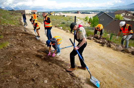 Ethan Blood, 15, of Lehi, packs down soil as he and volunteers help to complete his Eagle Scout Service Project that aims to create a walkable path connecting nearby neighborhoods to Ignite Entrepreneurship Academy and a future park Wednesday, May 8, 2019, just northwest of the charter school in Lehi, Utah. (Isaac Hale/The Daily Herald via AP)