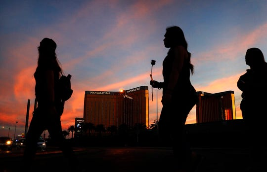 FILE - In this April 1, 2018, file photo, people carry flowers as they walk near the Mandalay Bay hotel and casino during a vigil for victims and survivors of a mass shooting in Las Vegas. Casino giant MGM Resorts is telling federal regulators it thinks it might pay up to $800 million to settle liability lawsuits stemming from the October 2017 mass shooting that became the deadliest in modern U.S. history. (AP Photo/John Locher, File)