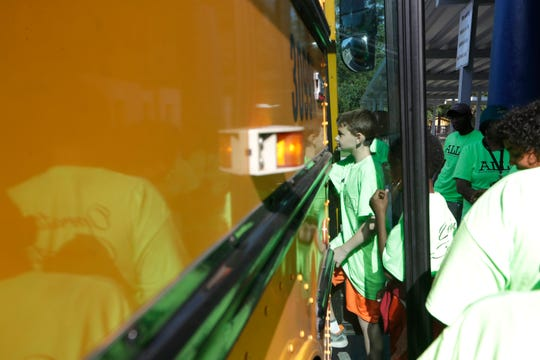 Students board a school bus as they get ready to leave for a field trip.