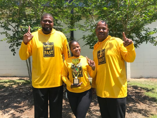 Nims Middle School track & field coaches Jeffery Sims (left), Shanya Charles and Daron Parrish celebrate with the state championship trophy.