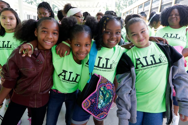 Jadelyn Yarbrough, a Pineview Elementary student, 11, left,  her friends Ka'Zariyah Willams, 9, Nykeria Norton, 9, and Katherine Cubas, 9, pose for a photo before boarding a bus headed to Wild Adventures Friday, May 17, 2019. The top 20 most academically improved students from both Pineview Elementary and Oak Ridge Elementary received a trip to Wild Adventures with sheriffs from the Leon County Sheriffs Office.