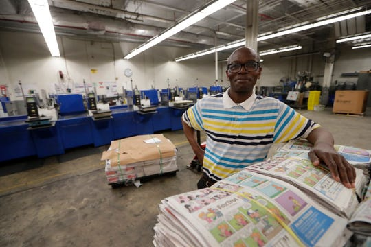 Theo Kayiranga, the packaging machine operator for the Tallahassee Democrat, poses for a photo in front of the insert stations Friday, May 17, 2019.