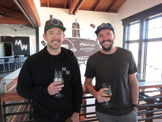MadeWest Brewing Co. co-founders Mike Morrison, left, and Seth Gibson pose in the brewery's new, off-site taproom on the second floor of Beach House Fish on the Ventura Pier. Morrison, who serves as head brewer, and Gibson, the brewery's CEO, opened the original facility and taproom in 2016 with co-founder Scott Chenoweth, who created the mural seen in the background.