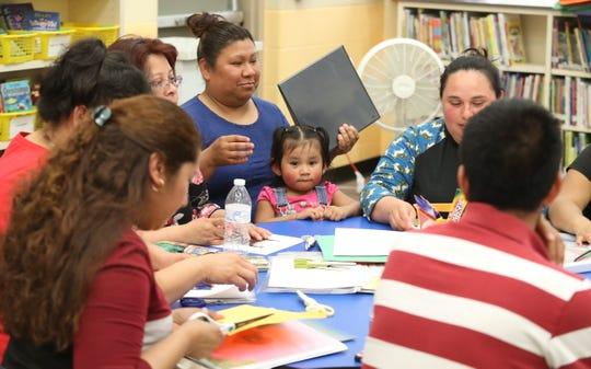 Padres de familia de habla hispana de la escuela primaria Blades Elementary asisten a una reunion semanal del programa Latino Family Literacy Project en la biblioteca de la escuela. Padres del programa leen libros infantiles en dos idiomas antes de llevarlos a casa y leerlos con los estudiantes.