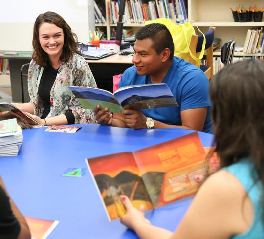 Lyndsey Gerstle, English Language Learner teacher and translator Luis Mier work with Spanish-speaking parents of Blades Elementary School students as they attend a weekly gathering of the Latino Family Literacy Project in the school's library.