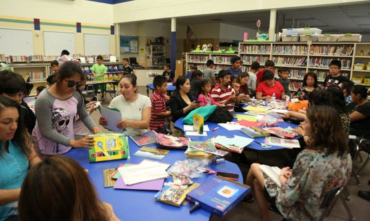 Spanish-speaking parents of Blades Elementary School students are joined by their children at the end of their weekly gathering of the Latino Family Literacy Project in the school's library.