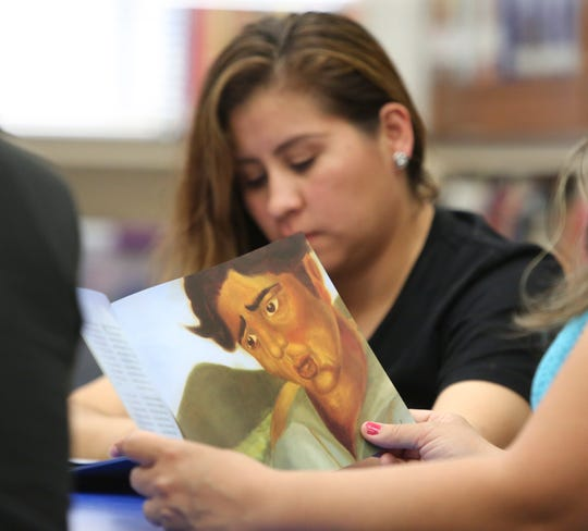 Spanish-speaking parents of Blades Elementary School students attend a weekly gathering of the Latino Family Literacy Project in the school's library.