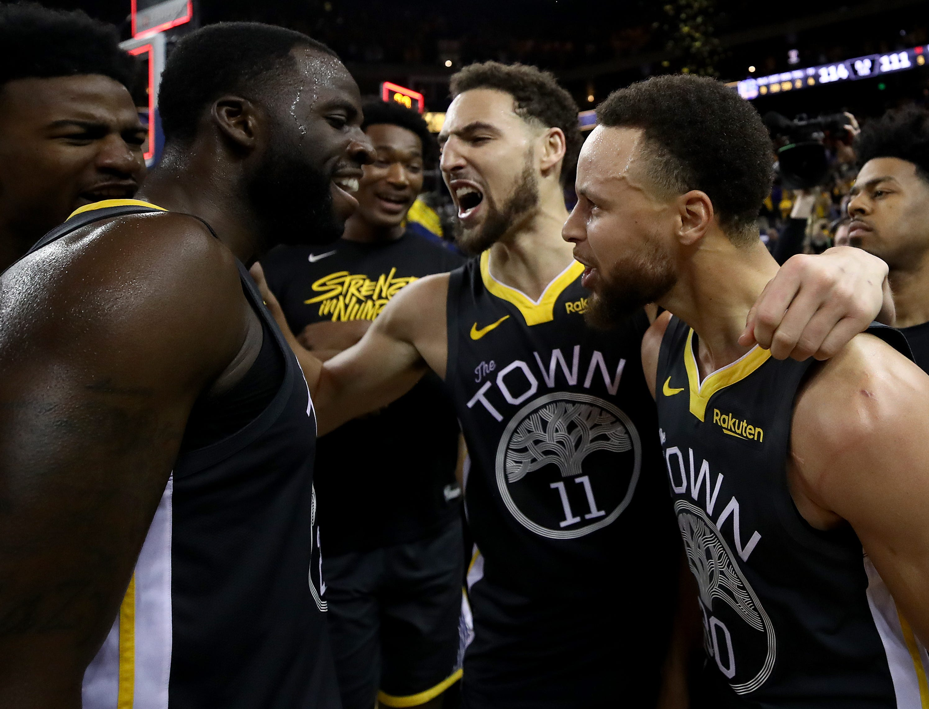 Stephen Curry, Klay Thompson and Draymond Green celebrate.