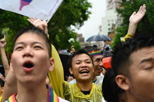 "Gay rights supporters celebrate outside Parliament after lawmakers legalised same-sex marriage bill in Taipei on May 17, 2019. - Taiwan's parliament began debating Asia's first gay marriage law as conservative lawmakers launch a last-ditch attempt to scupper the most progressive bill in favour of a watered-down ""civil-union"" law."