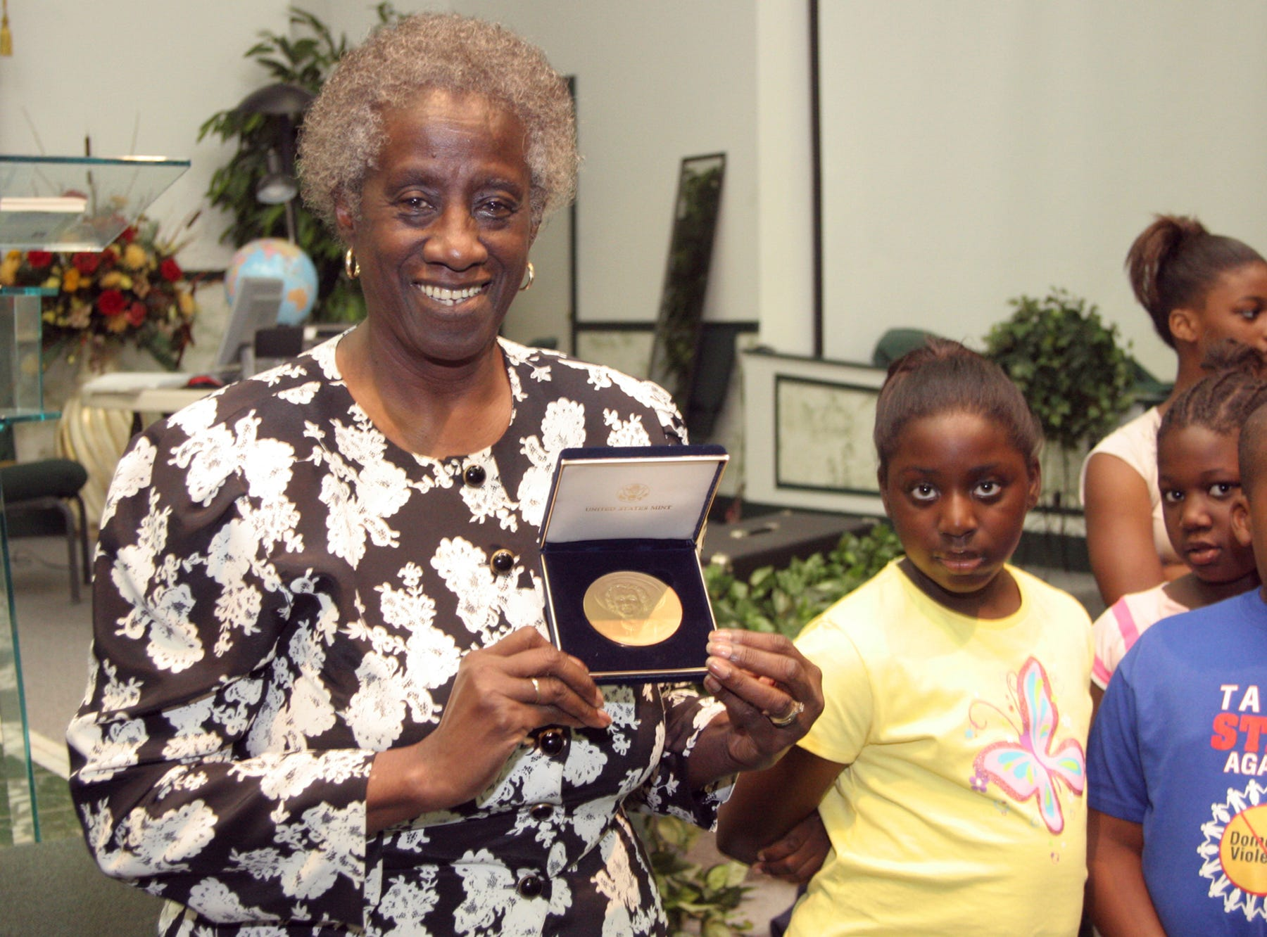 In a Tuesday, July 25, 2006 file photo, Unita Blackwell, left, the first black woman mayor in the state of Mississippi, shows an audience the gold minted coin given to her in recognition of her pioneering struggles for voters rights, in Greenville, Miss. Unita Blackwell, a civil rights activist who was the first African American woman to win a mayor's race in Mississippi , died Monday, May 13, 2019  in Ocean Springs Hospital. She was 86.