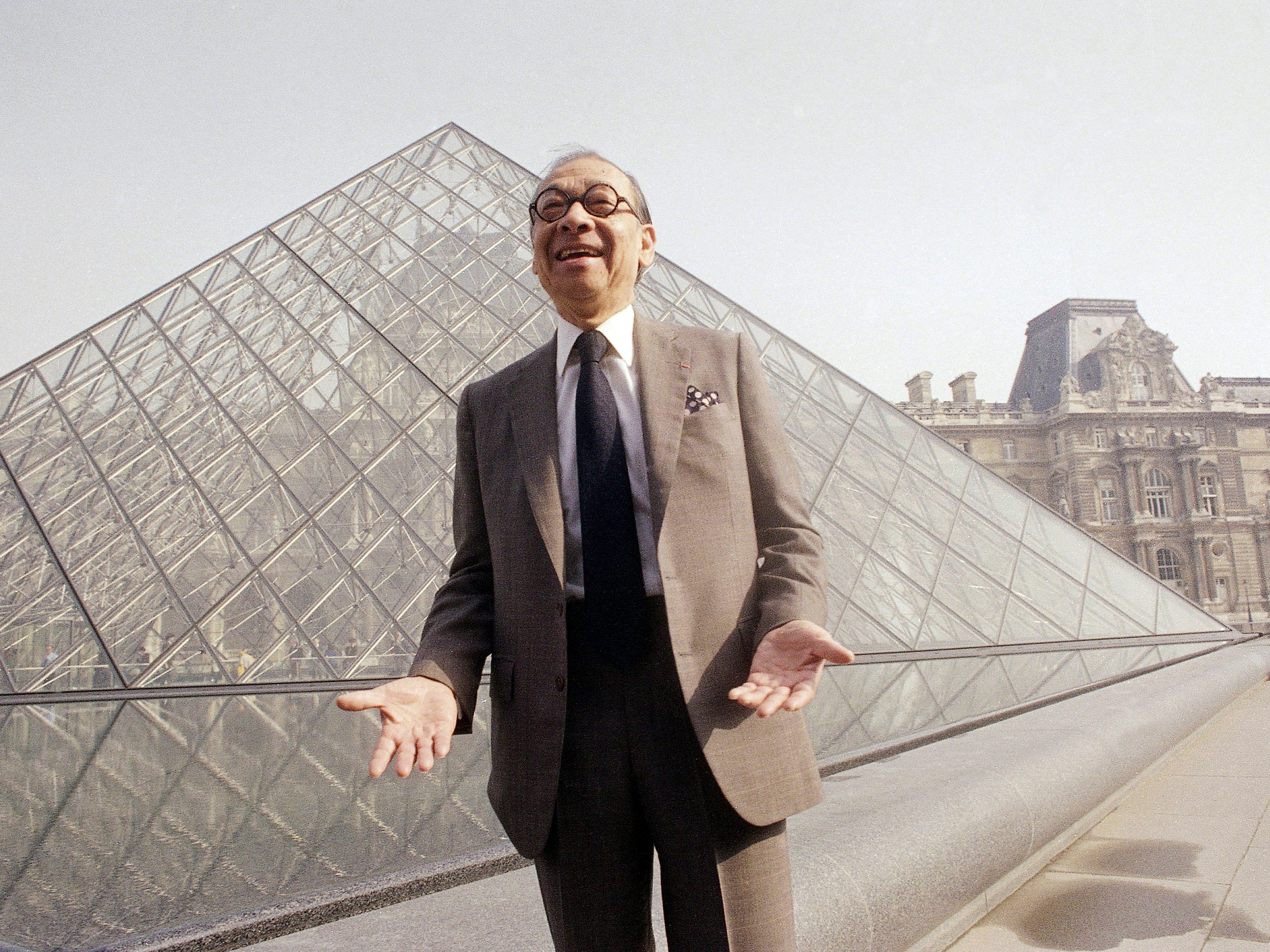 In this March 29, 1989, file photo, Chinese-American architect I.M. Pei laughs while posing for a portrait in front of the Louvre glass pyramid, which he designed, in the museum's Napoleon Courtyard, prior to its inauguration in Paris. Pei, the globe-trotting architect who revived the Louvre museum in Paris with a giant glass pyramid and captured the spirit of rebellion at the multi-shaped Rock and Roll Hall of Fame, has died at age 102, a spokesman confirmed Thursday, May 16, 2019.