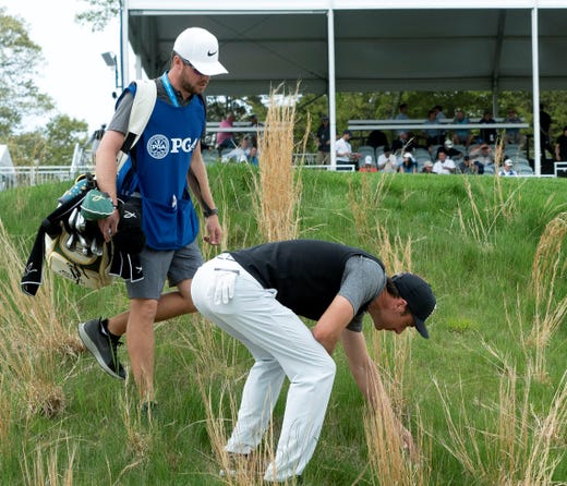 Second round: Ross Fisher and caddie Will Davidson look for his ball in the rough on the 18th hole.