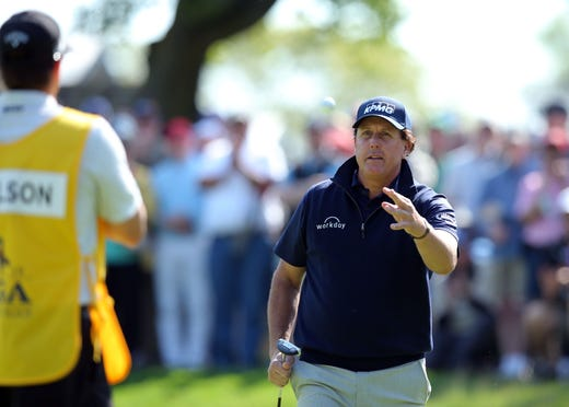 Second round: Phil Mickelson tosses his ball to his caddie Tim Mickelson after the 14th hole.