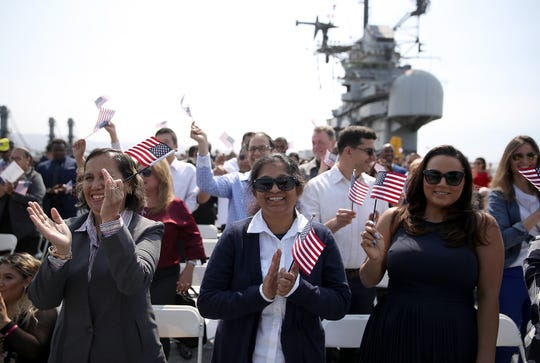 Immigrants celebrate after being sworn in as American citizens during a naturalization ceremony on the flight deck of the USS Hornet on July 3, 2018 in Alameda, California