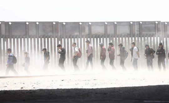 Migrants walk while being detained by Border Patrol after crossing to the U.S. side of the U.S.-Mexico border barrier on May 17, 2019 in El Paso, Texas.
