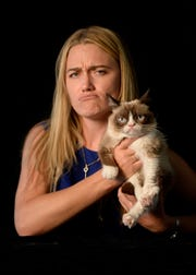 Grumpy Cat, whose real name was Tardar Sauce, poses with owner Tabatha Bundesen during a 2014 visit to USA TODAY's New York offices.