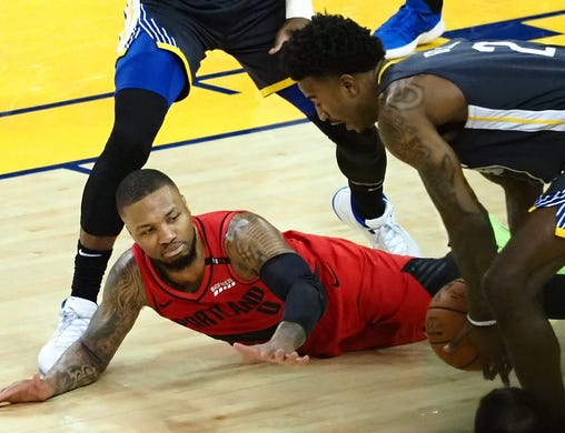 May 16: Warriors defender Jordan Bell (2) steals the ball from Blazers guard Damian Lillard (0) as he falls to the floor during Game 2.